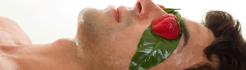 Mann mit Creme im Gesicht und Erdbeeren auf den Augen